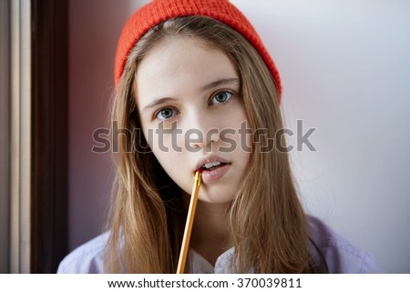 Young woman university student thinking and looking at camera. Caucasian female model - stock photo