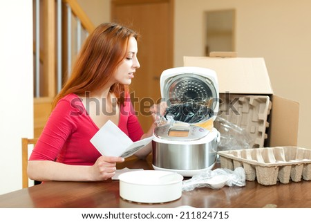 Young woman unpacking and reading user manual for new crock-pot at home - stock photo