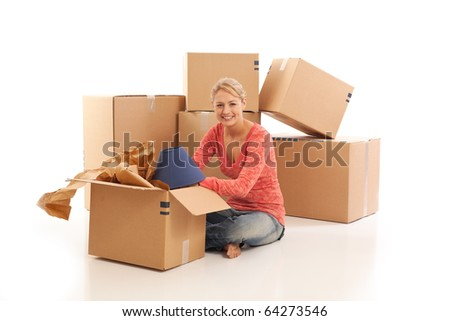Young woman unpacking cardboard boxes