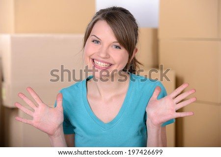 Young woman unpacking cardboard boxes after moving to new home - stock photo
