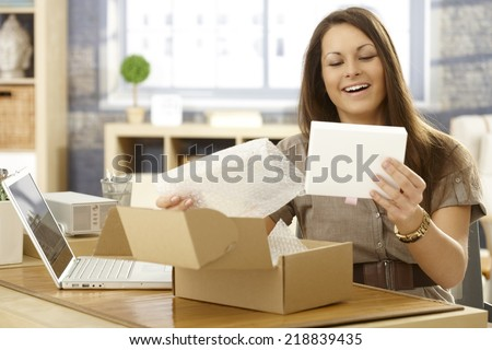 Young woman unpacking postal packet, smiling happy. - stock photo