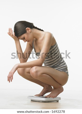 Young woman upset while reading weight on scale - stock photo