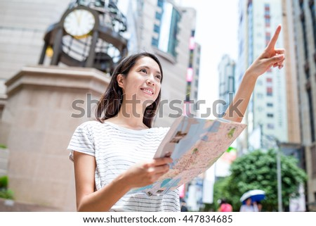 Young woman use of city map and finger pointing far away - stock photo