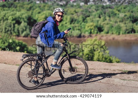 Young woman use of the cellphone at countryside while cycling - stock photo