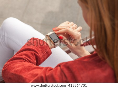 young woman use smartwatch with blank screen outdoor, view of shoulder - stock photo
