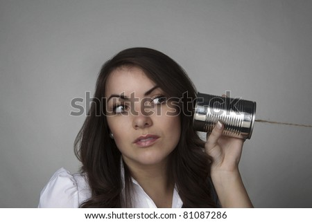 young woman useing a tin can string phone - stock photo