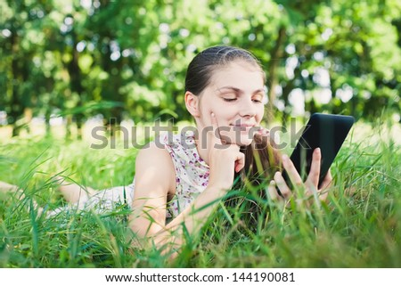 young woman uses a digital tablet on the nature
