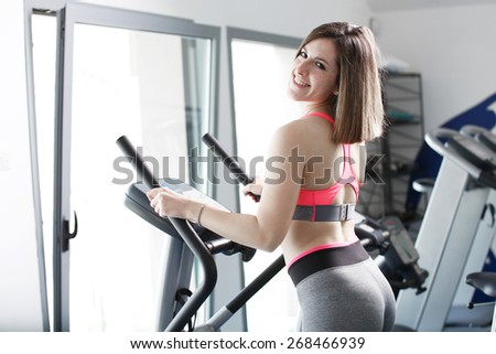 Young woman uses stationary bicycle trainer on gym - stock photo