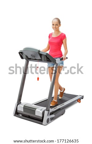 Young woman uses treadmill. - stock photo
