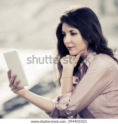 Young woman using a digital tablet computer outdoor - stock photo