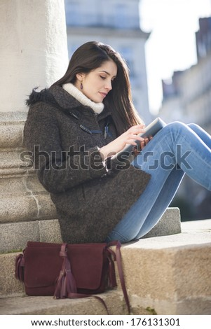 young woman using a digital tablet outside