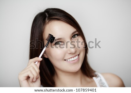 young woman using a eye brow and lash groomer with a big smile on her face - stock photo