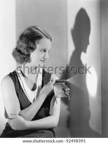 Young woman using a flashlight on her key chain - stock photo