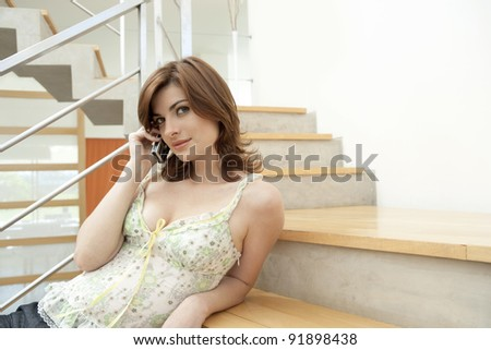 Young woman using a home phone while sitting on modern stairs.