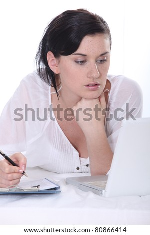 Young woman using a laptop computer and  a pen and paper - stock photo