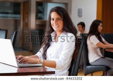 Young woman using a laptop in a cafe - stock photo