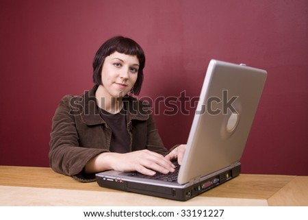 Young woman using a laptop in a home environment.