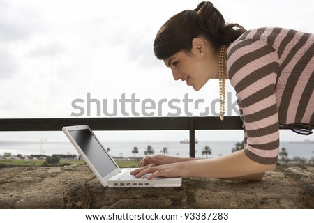 Young woman using a laptop outdoors, while on vacation.