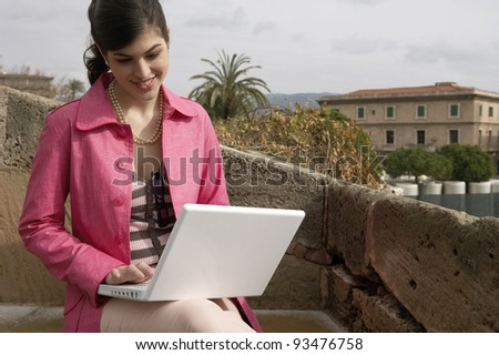 Young woman using a laptop outdoors, while on vacation. - stock photo