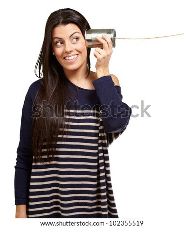 Young woman using a metal tin can over a white background - stock photo