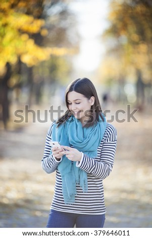 Young woman using a smart phone outdoors - stock photo