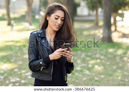 Young woman using a smartphone in an urban park. Girl wearing leather jacket. - stock photo