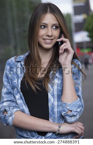 Young woman using a smartphone on the city - stock photo