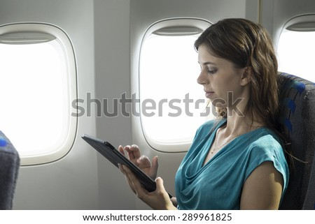 Young woman using a tablet/ipad on a plane - stock photo