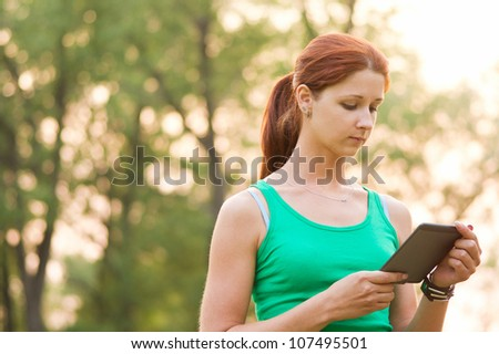 Young woman using a tablet outdoors - stock photo