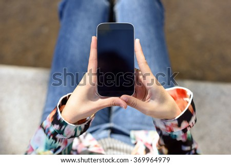 Young woman using a touchscreen smartphone wearing casual clothes