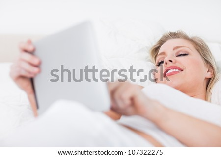 Young woman using an ebook while lying on her bed - stock photo