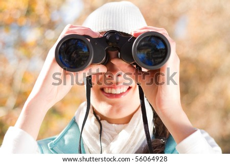 young woman using binoculars in autumn forest - stock photo