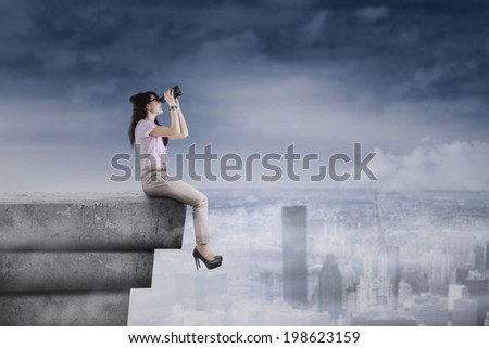 Young woman using binoculars on rooftop for looking her vision - stock photo