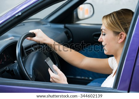 Young woman using cell phone while driving car - stock photo