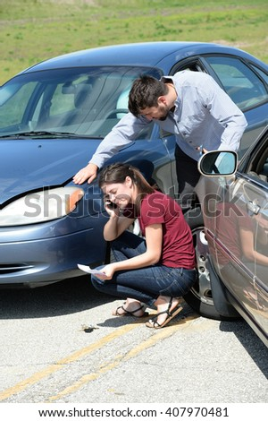 Young woman using cellphone after accident while man inspects damage - stock photo