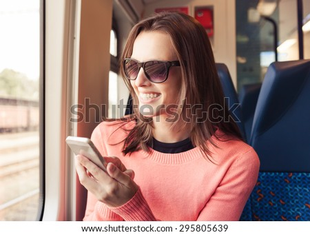 Young woman using cellphone while traveling by train.