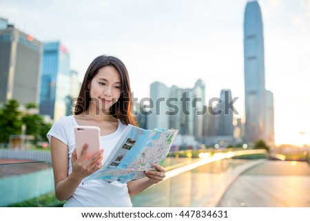 Young woman using city map and hold with cellphone - stock photo