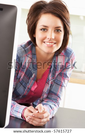 Young Woman Using Computer In Modern Kitchen - stock photo