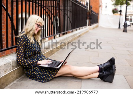 young woman using computer in the street.  - stock photo