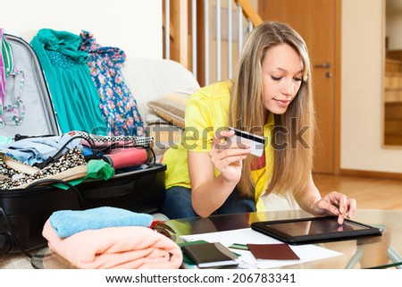 Young woman using credit card and tablet for reserving plane ticket online - stock photo