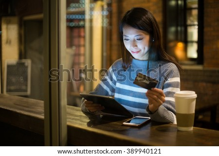 Young woman using credit card for paying on tablet - stock photo