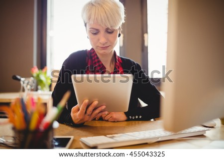 Young woman using digital tablet at office - stock photo