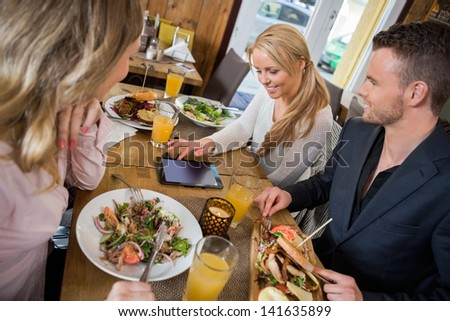Young woman using digital tablet while having meal with colleagues at cafe - stock photo