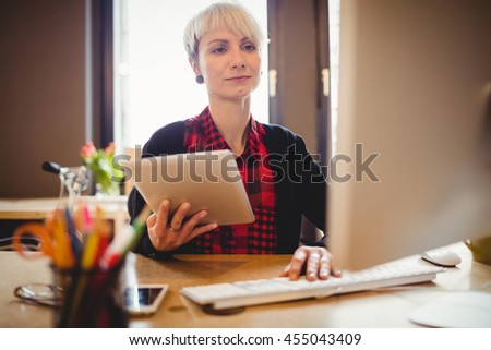 Young woman using digital tablet while working on computer at office - stock photo