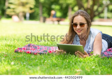 Young woman using digital tablet. Woman looks at a digital tablet in a summer park lie on the green grass. Beautiful girl smiling.