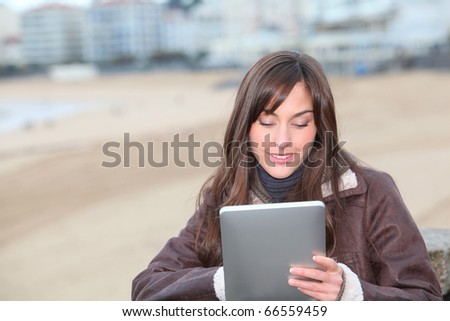 Young woman using electronic pad by the beach in winter - stock photo