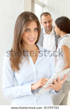 Young woman using electronic tablet in meeting - stock photo