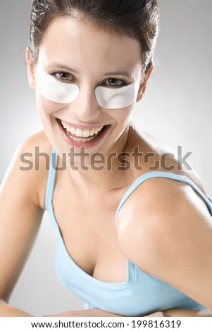 Young woman using eye pads, smiling, close up - stock photo