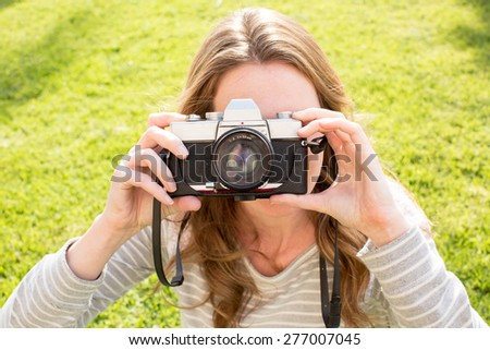 Young woman using her antique camera - stock photo