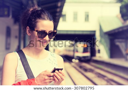 Young woman using her cell phone on subway platform, checking message sms e-mail or train schedule. Girl texting on smartphone